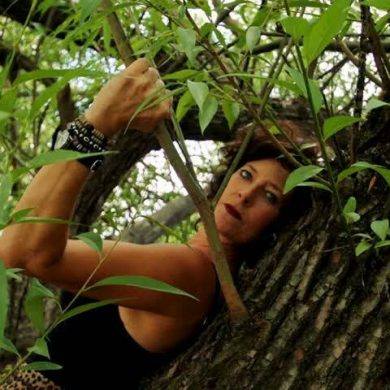 Kelly leaning against a tree